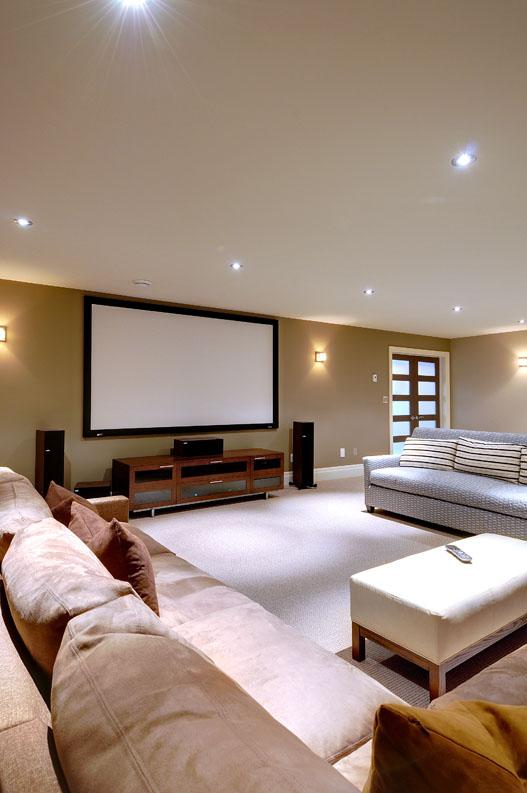 Fixed screen family room home theatre system with Lutron lighting control.